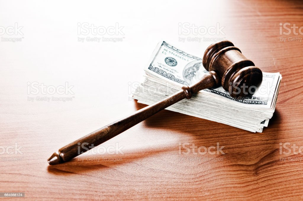 Judge's or auctioneer's wooden gavel resting on stack of banknotes stock photo