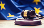Judges wooden gavel with EU flag in the background.