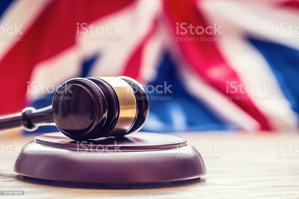 Judges wooden gavel with UK flag in the background. stock photo