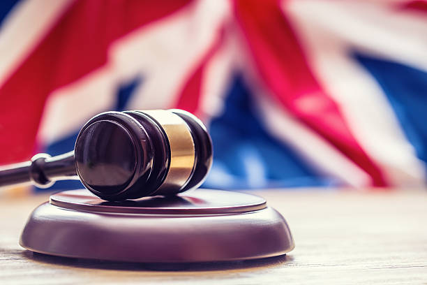 Judges wooden gavel with UK flag in the background. – Foto