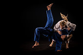 Photo of a woman in a white kimono throwing her sparring partner in a blue kimono to the ground. Black background.