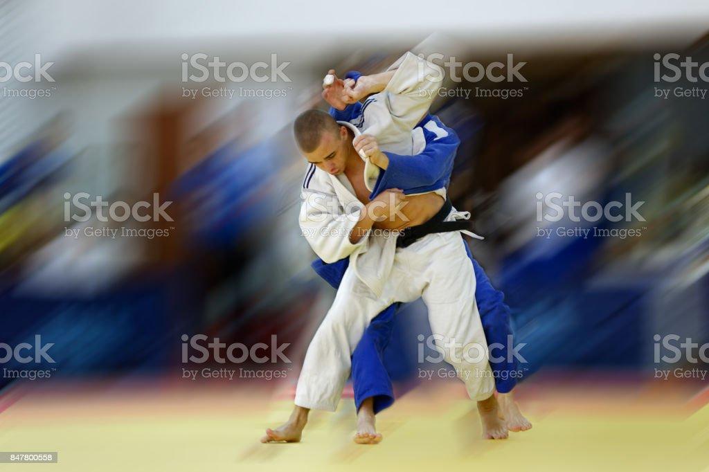 Judoka in white judogi attempting to throw opponent in blue judogi with Sode Tsurikomi Goshi stock photo
