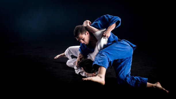 Judokas wrestling on the ground after throw Two judokas in blue and white kimonos wrestling on the ground during a sparring duel. Black background. brazilian culture stock pictures, royalty-free photos & images