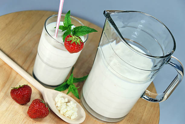 Jug and glass of kefir, decorated with fresh strawberries stock photo