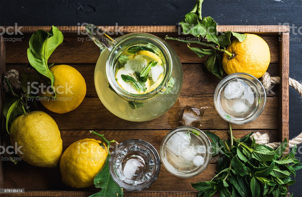 Jug and glasses with homemade lemonade, ice cubes on wooden stock photo
