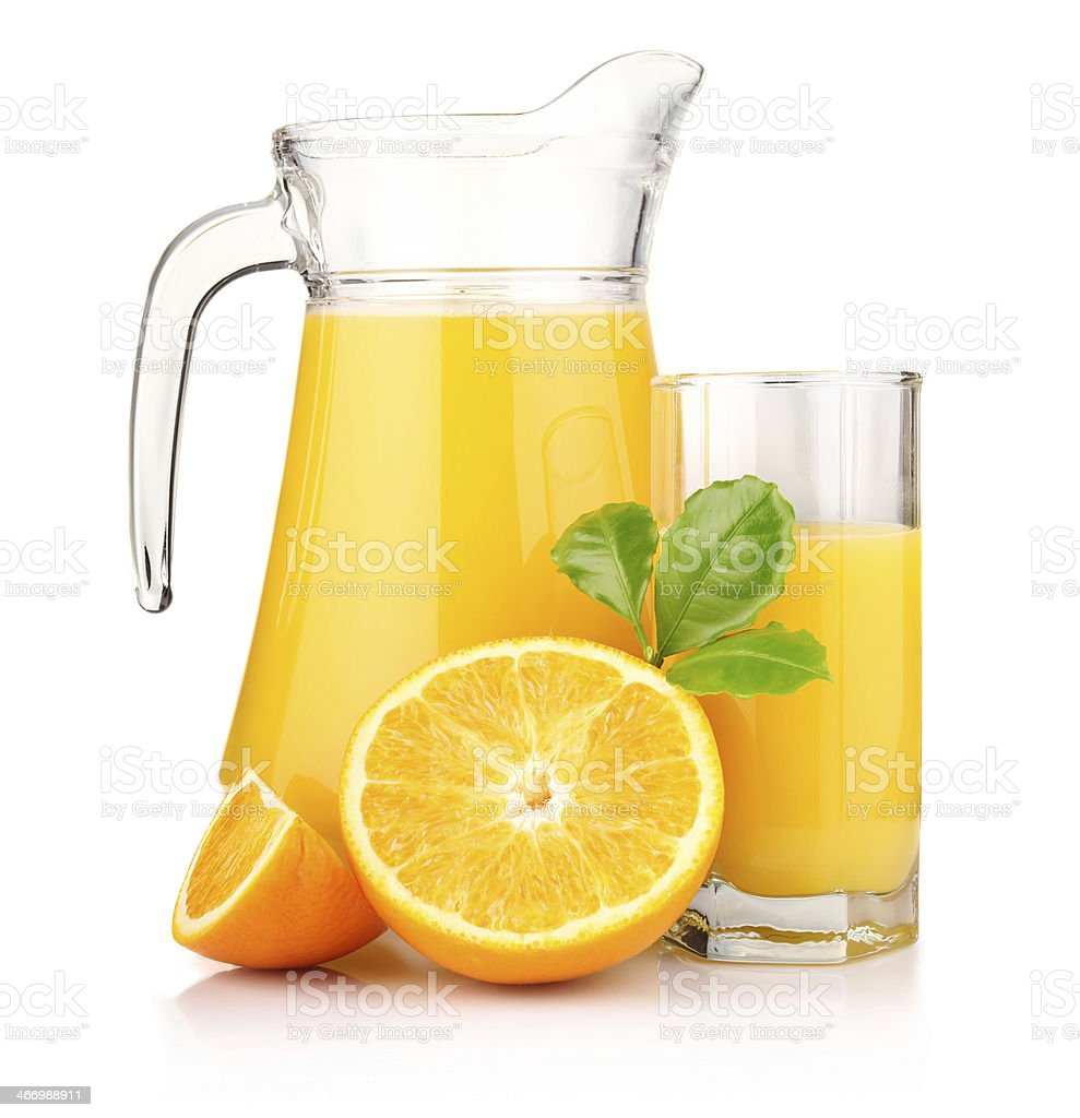 Jug, glass of orange juice and fruits with green leaves royalty-free stock photo