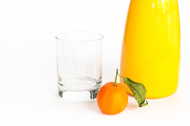 Jug of juice, glass and an orange