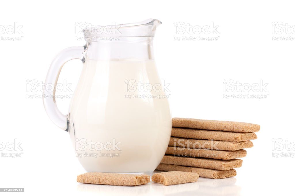 jug of milk with stack of grain crispbreads isolated on white background stock photo