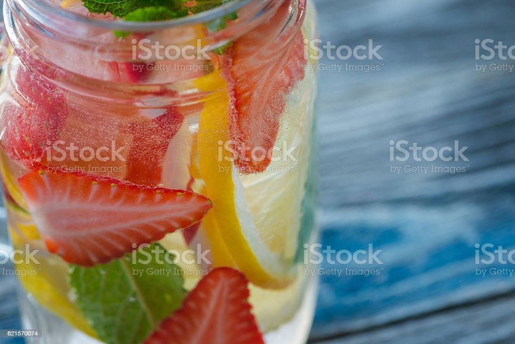 Jug with lemon and strawberry infused water photo libre de droits