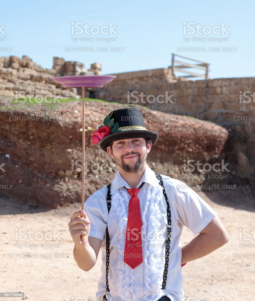 A juggler - participant of the Purim festival shows performance for visitors in ruins of old city Caesarea, Israel stock photo