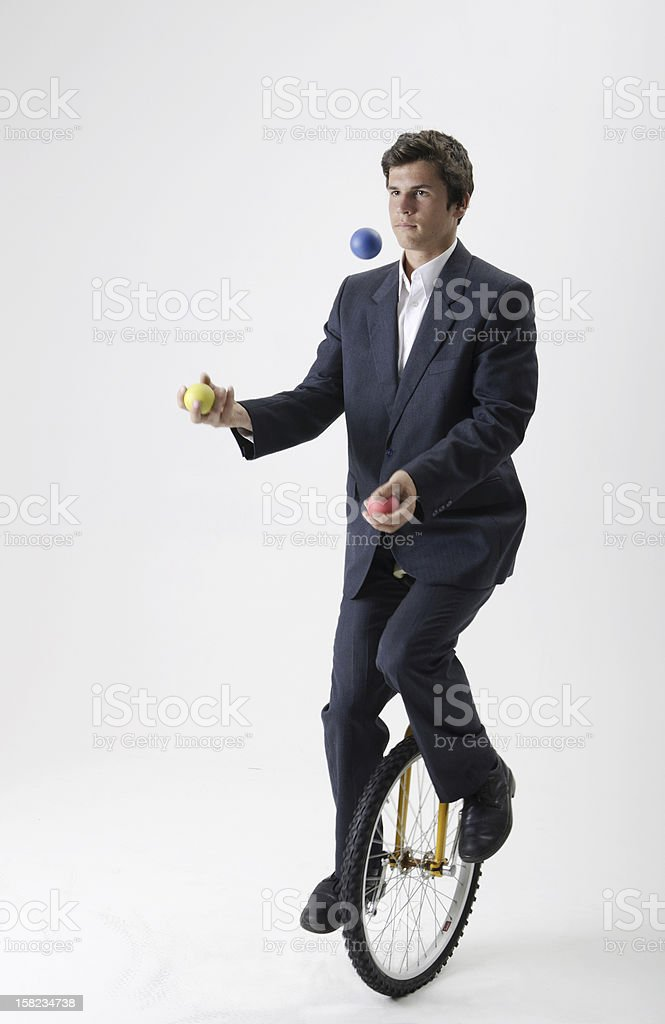 Juggling businessman on unicycle royalty-free stock photo