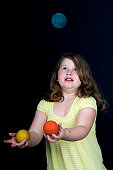 Girl aged 9 to 10 years juggling with three multicolored juggling balls, black background.