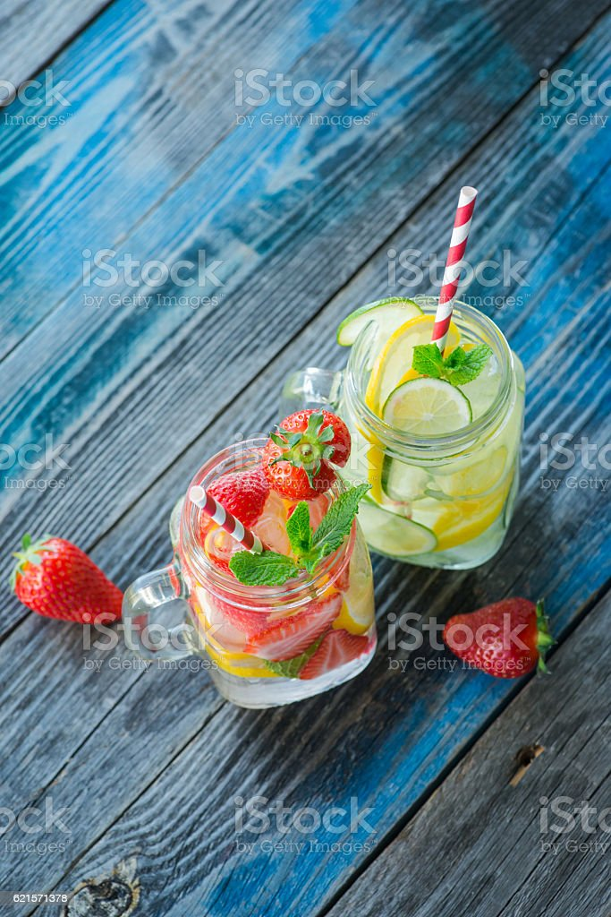 Jugs with lemon, lime and strawberry infused water photo libre de droits