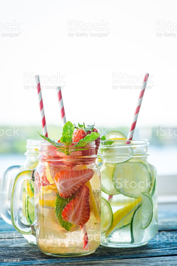 Jugs with lemon, lime, strawberry and cucumber infused water photo libre de droits