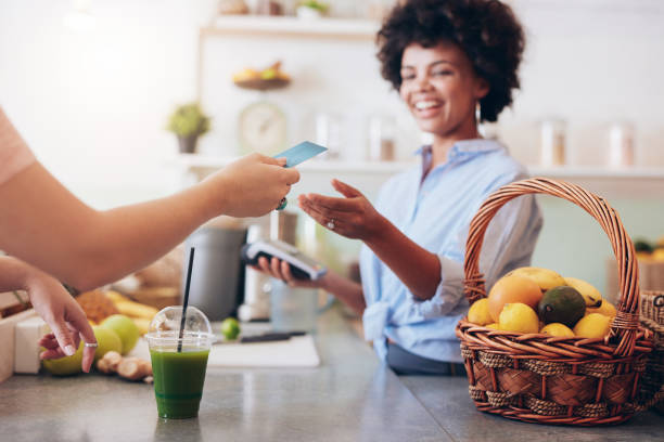 juice bar owner taking payment from customer - paying with card contactless imagens e fotografias de stock