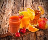 Fresh fruits juices on wood plant, strawberry, orange and apple drinks