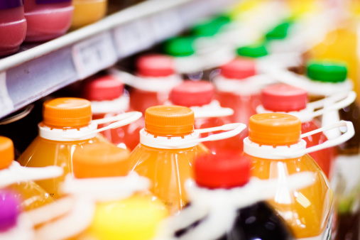 Abstract shot of many bottles of juice on refrigerated shelves at a supermarket. Camera: Canon EOS 1Ds Mark III.