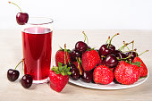 Juice in a glass and fresh ripe strawberries and cherries