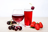 Juice in a glass and ripe fresh berries cherries and strawberries