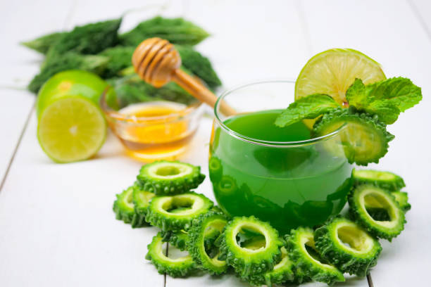 Juice of bitter gourd with raw and sliced bitter gourd.Healthy Herbal Drink stock photo