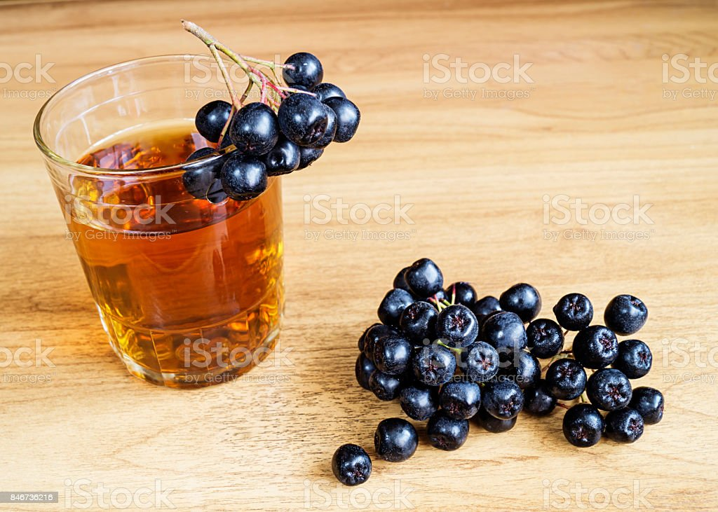 Juice of rowanberry in cup on table stock photo