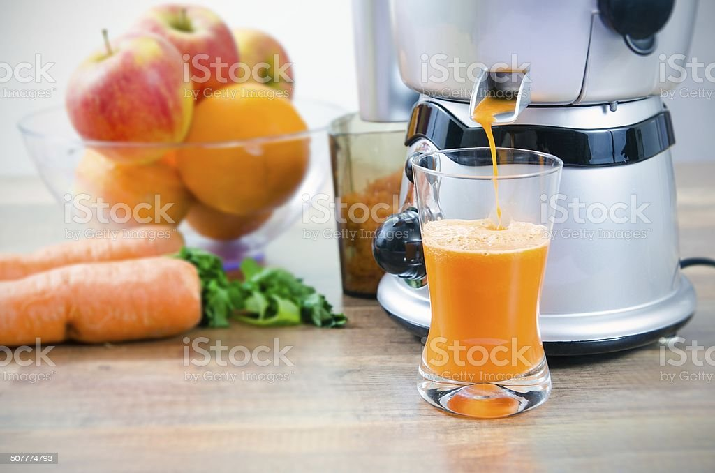 Juicer and carrot juice. Fruits in background stock photo