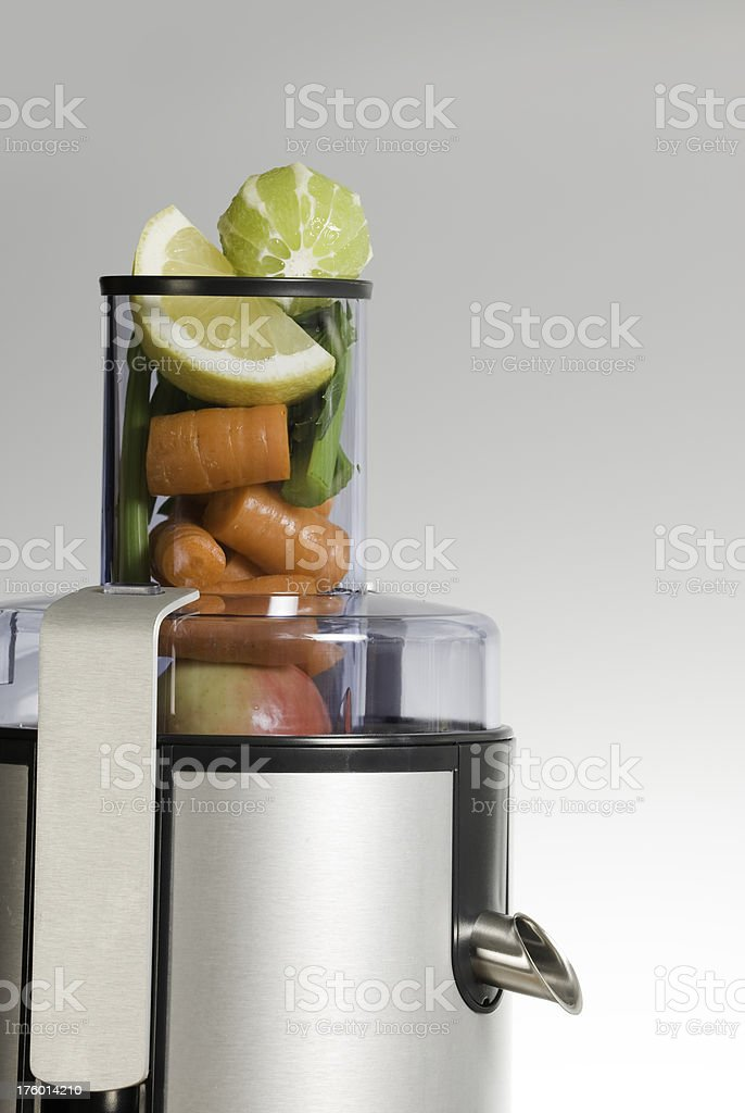 Juicer being filled with fresh fruit and vegetables royalty-free stock photo