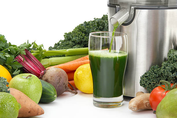 Juicer pouring juice into glass surrounded by vegetables Juicing fresh organic vegetables and fruit for healthy living. vegetable juice stock pictures, royalty-free photos & images