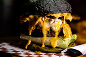 Juicy and greasy rustic cheese burger with mayonnaise melting inside grilled beef meat and lettuce with dark charcoal bun