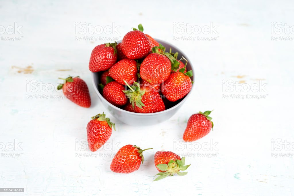 Juicy and ripe strawberry in bowl on wooden background stock photo