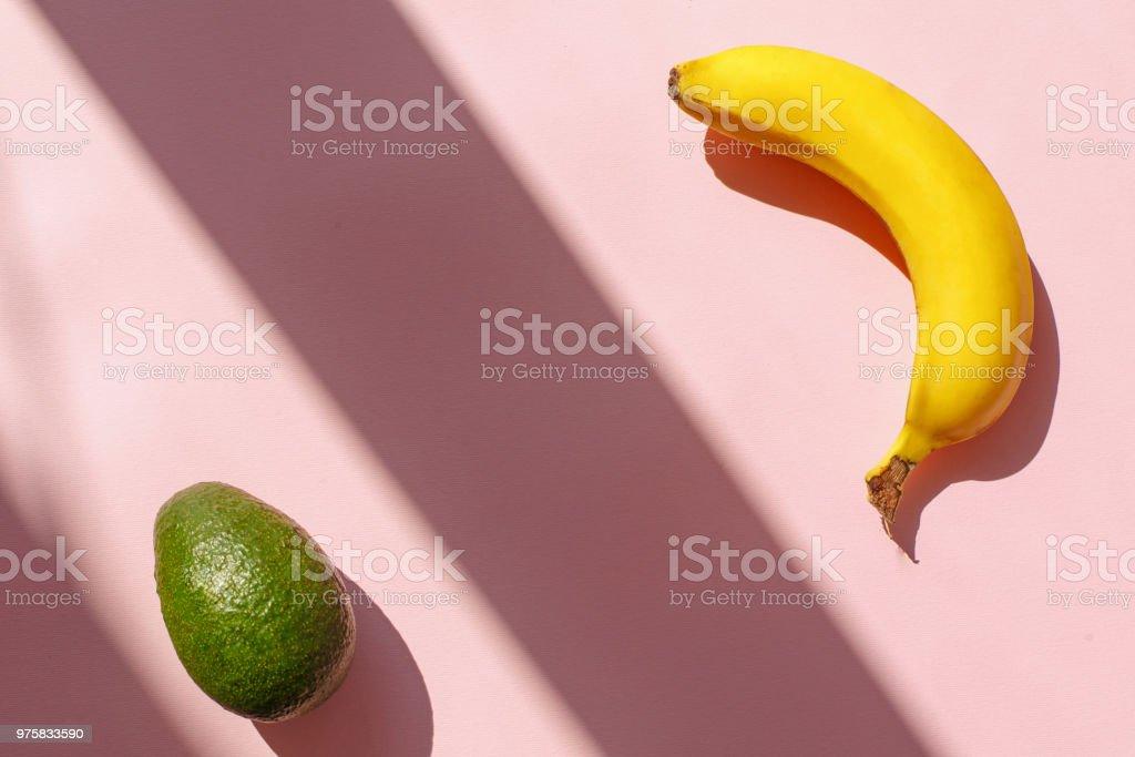 saftige Avocado und Banane auf trendige Rosa Papierhintergrund im Sonnenlicht. flach lag. kreativen Kontrast Sommer Bild. Urlaub und Diät-Konzept. Platz für Text. Tropischer Sommerurlaub - Lizenzfrei Avocado Stock-Foto