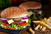 juicy beef burger, french fries, wooden board