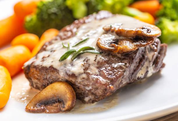 Juicy Beef Rib Eye Steak mit Pilzsauce und Babygemüse – Foto