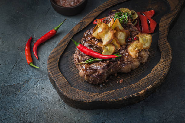 Juicy beef steak served on wooden board with crispy potatoe chips and chilli stock photo