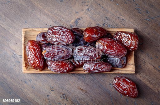 istock Juicy dates on wooden table . 896965482
