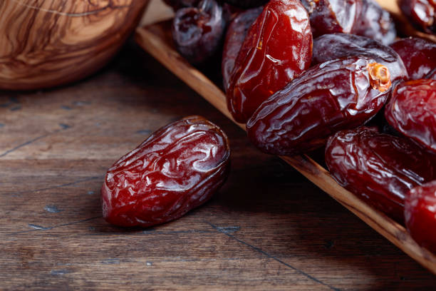 Juicy dates on wooden table . stock photo