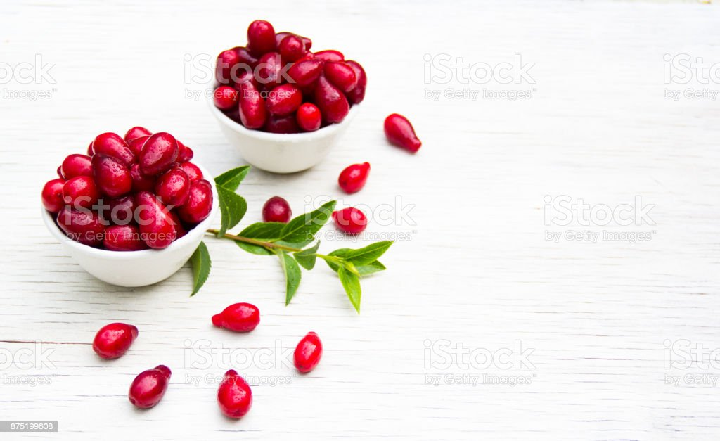 Juicy dogwood in white bowls on a white table. Copy space stock photo