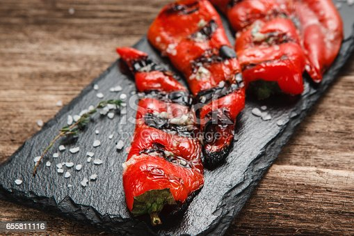 655794674 istock photo Juicy fresh grilled paprika served on wood table 655811116