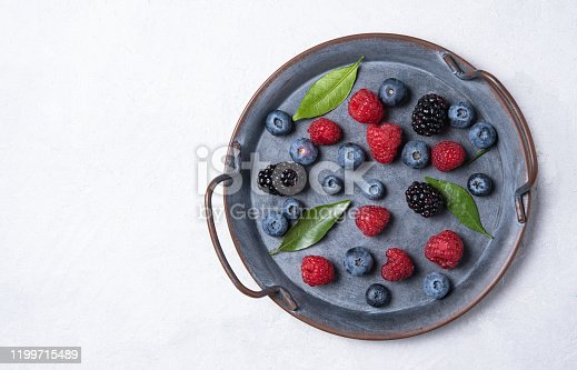 863562090 istock photo juicy fresh raspberries, blueberries, blackberries and mint leaves lie in  a blue plate on a white table 1199715489