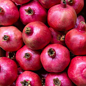 Ripe fruits of tropical pomegranates in wooden boxes close-up. Selective focus.