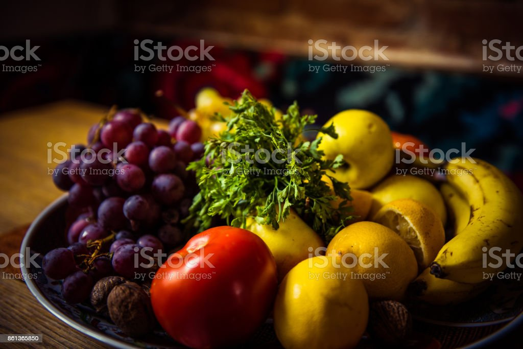 Juicy grapes, apples, lemons, nuts, banana, tomato and parsley on a plate stock photo