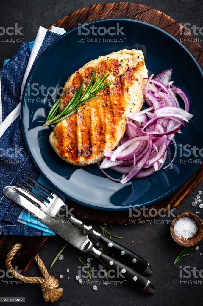Juicy grilled chicken meat, fillet with fresh marinated onion on plate. Black background, top view stock photo