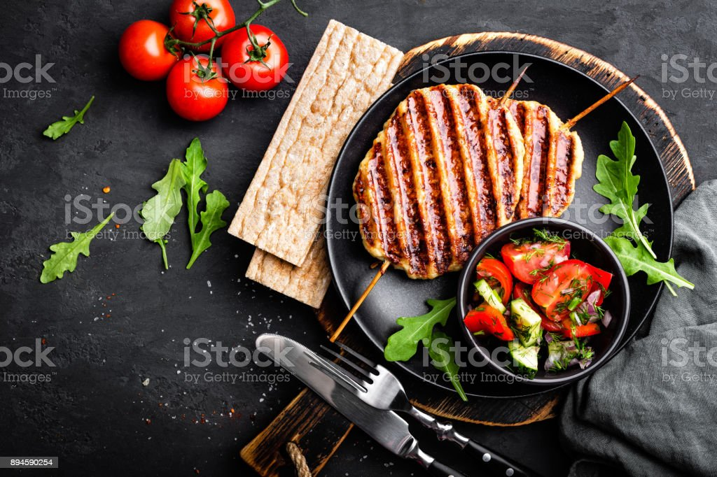 Juicy grilled chicken meat lula kebab on skewers with fresh vegetable salad on black background, top view stock photo