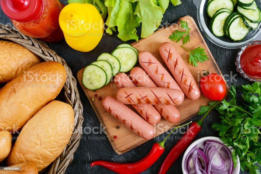 Juicy grilled sausages, sauces, fresh vegetables, crispy buns, on a wooden background. Top view. Flatlay. Ingredients for a hot dog. Street food. stock photo