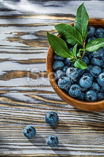 Juicy huckleberries in round wooden bowl.