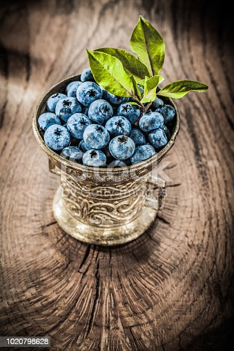 Juicy huckleberries in vintage metal bowl on grunge board.