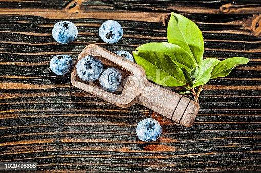 Juicy huckleberries in wooden spoon.