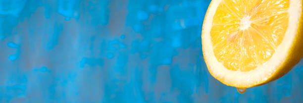 Saftige Zitronenfrucht, Nahaufnahme, blauer Hintergrund, Panoramaformat mit gutem Kopierplatz – Foto