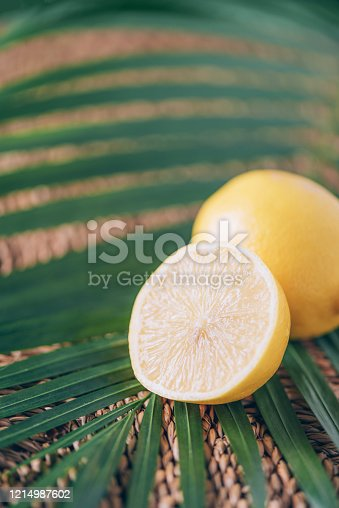 Juicy lemons with green palm leaves on rattan background. Copy space. Christmas or New year concept Lemon fruit, citrus minimal concept, vitamin C