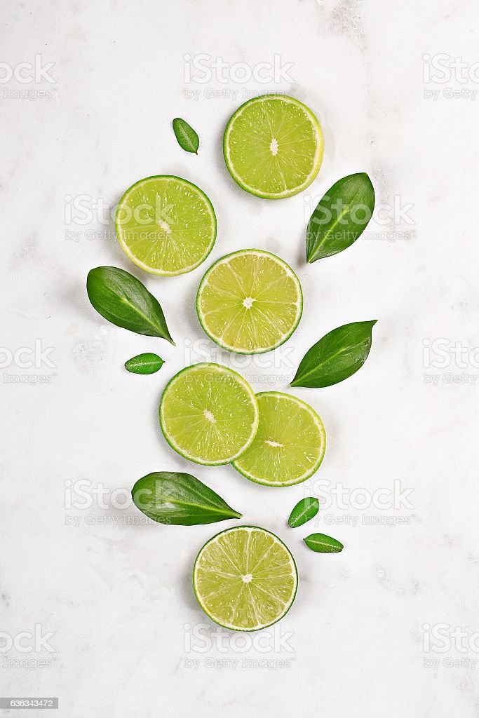 Juicy lime slices flat lay on marble background. Top view stock photo